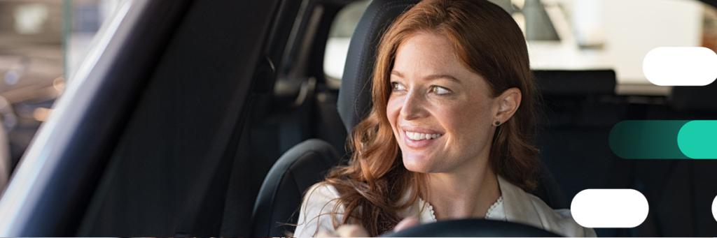 uśmiechnięta kobieta za kierownicą
